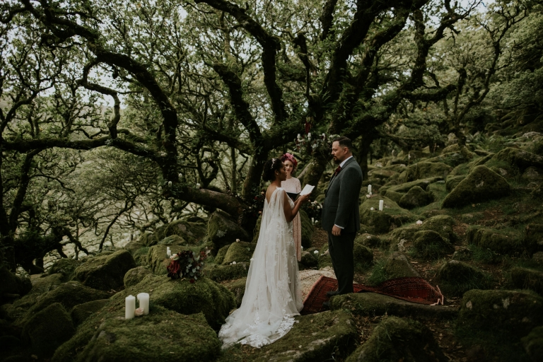 ceremony in woods, moss covered rocks and candles