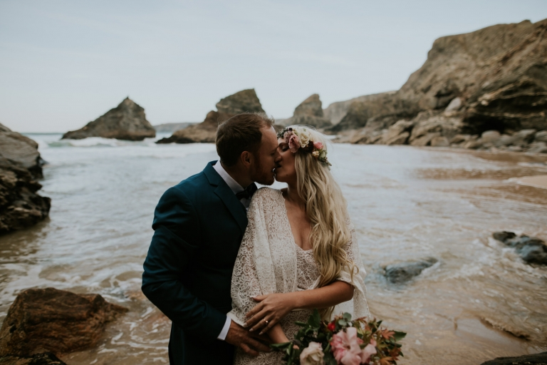 couple kissing passionately on Cornwall beach during their wedding