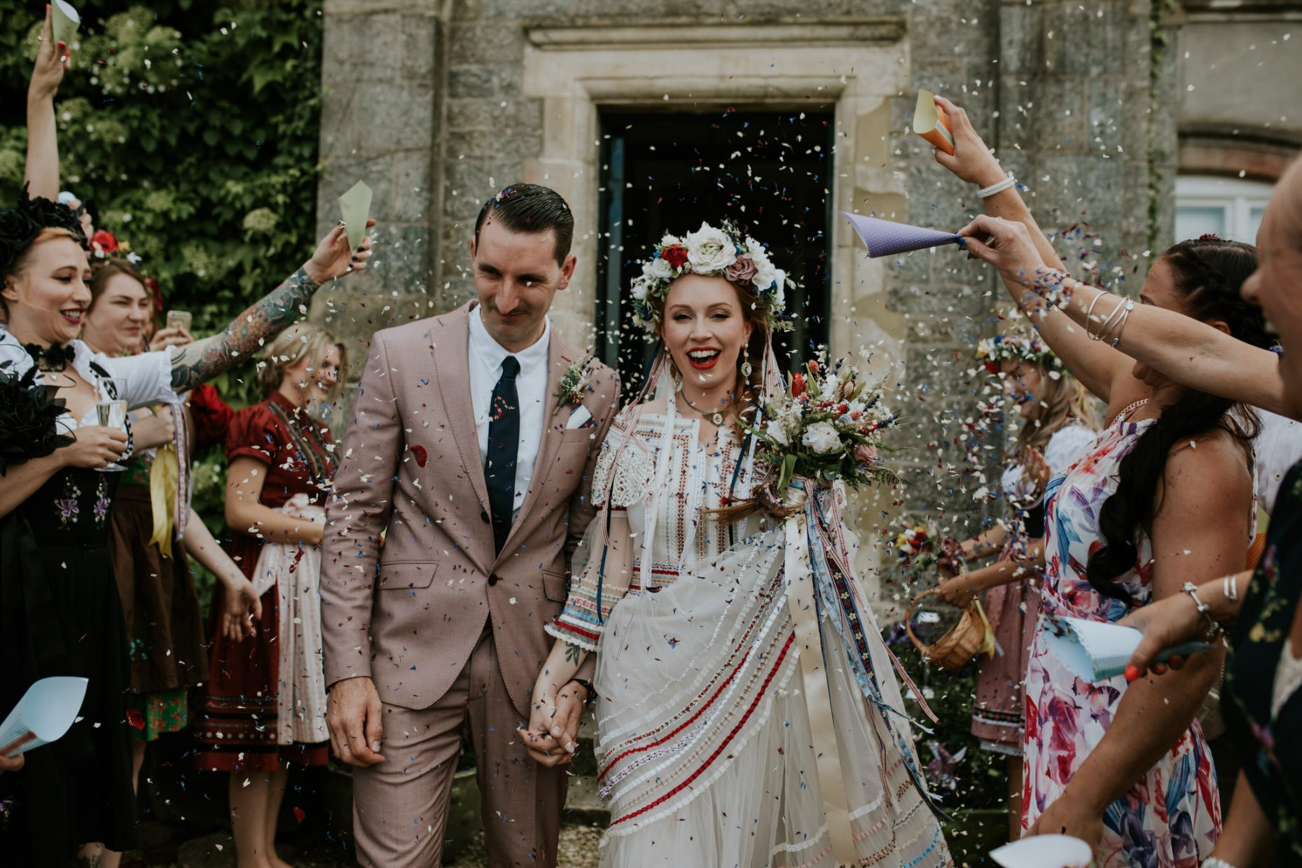 bride and groom have confetti thrown in their faces with big smiles on their faces and wildflowers in her hair
