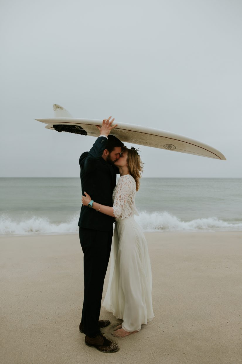 A bride and groom kiss passionately under a surfboard to shelter from the rain on the beach
