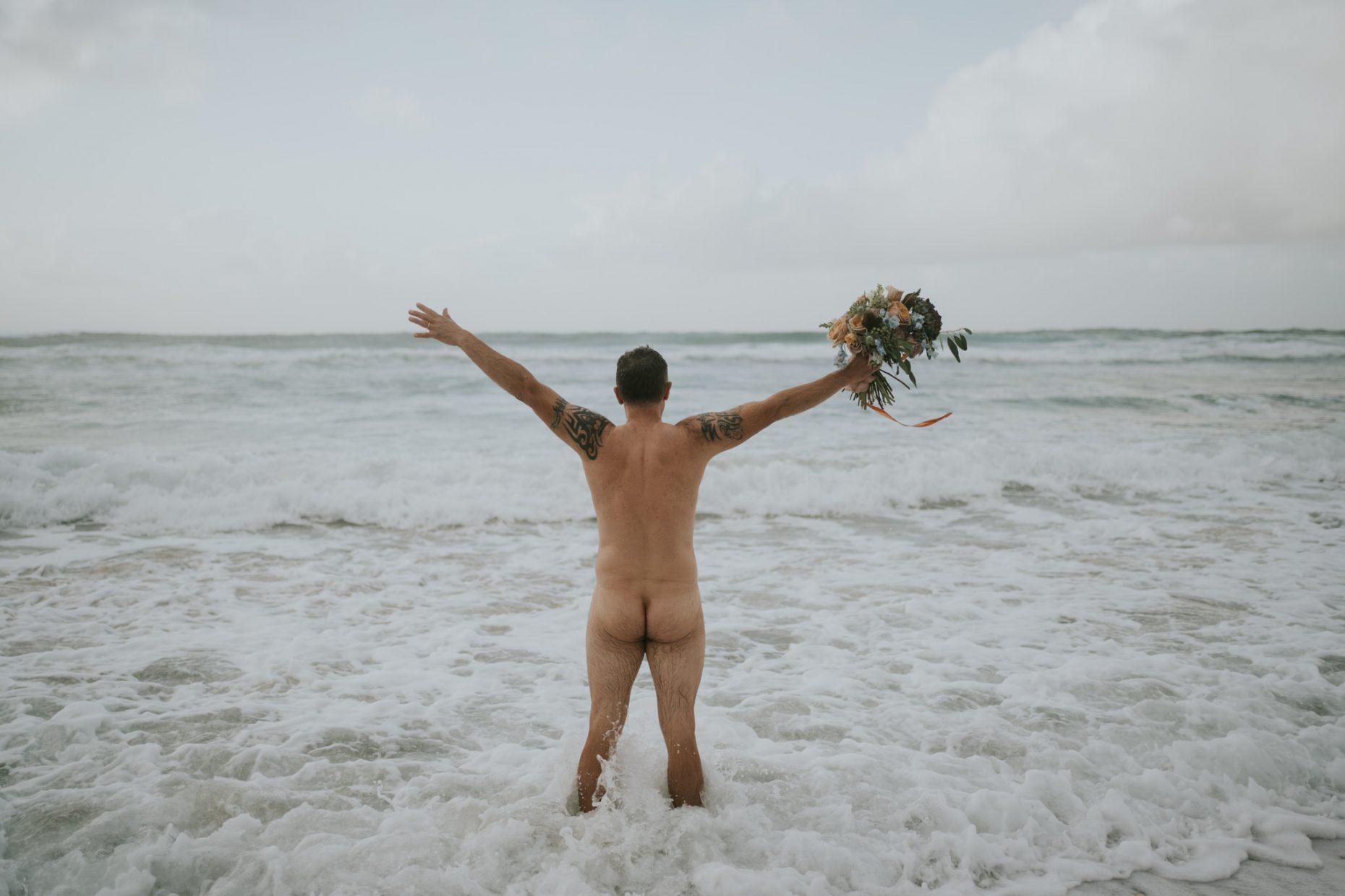 a groom runs naked into the sea as the wave splashes him and he holds his brides bouquet in the air