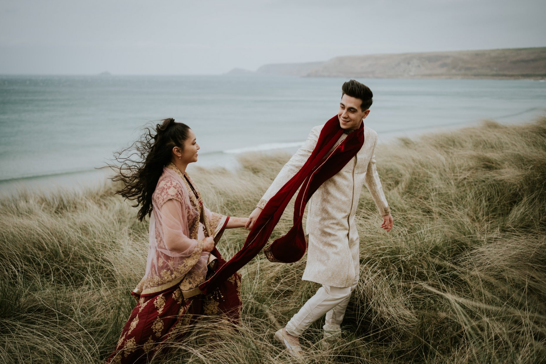 Bride and groom walk hand in hand in traditional Indian wedding clothes through the long grass in sanddunes