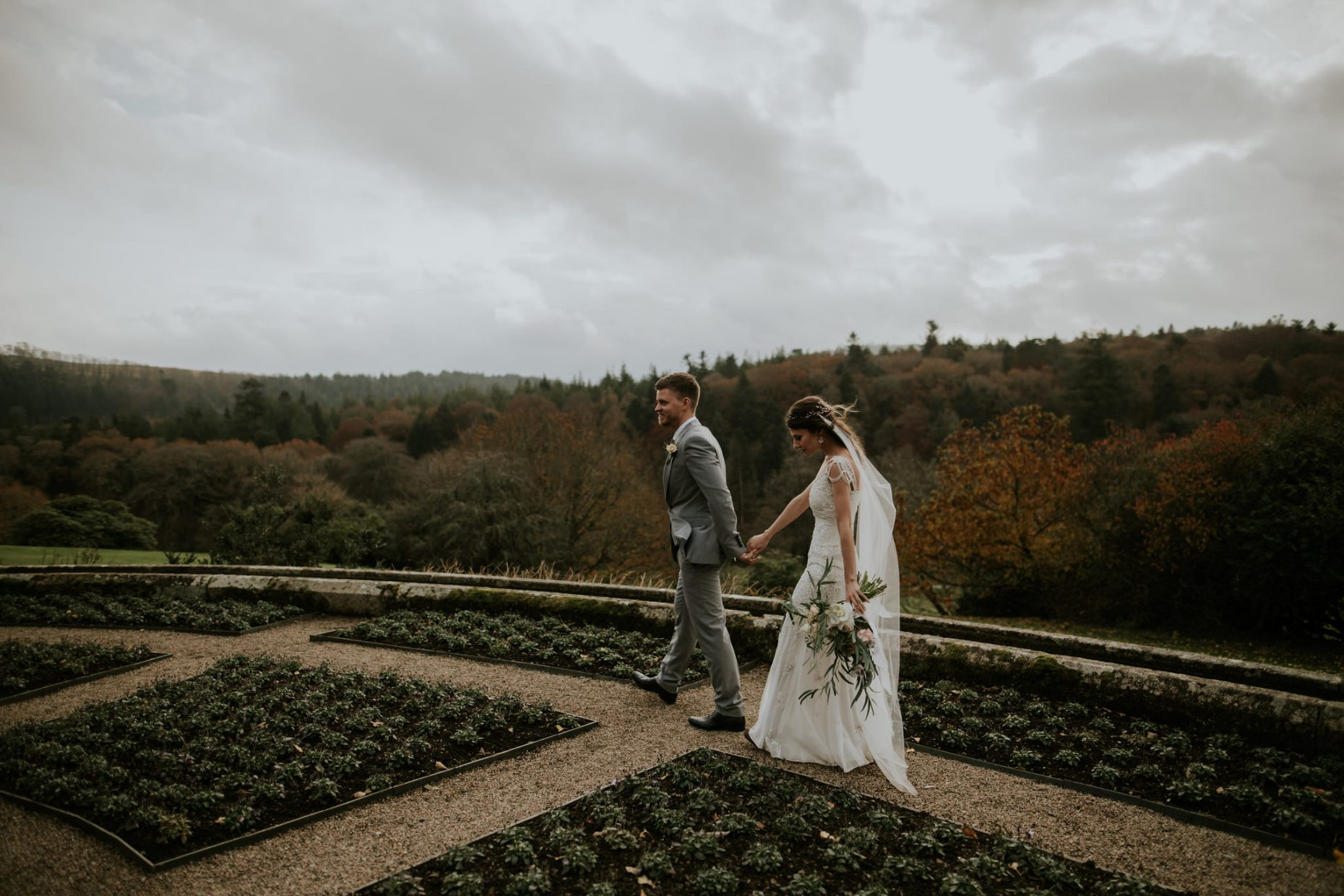 groom holds brides hand and leads her through a beautiful manicured ancient garden as the wind blows and gently catches her hair and veil