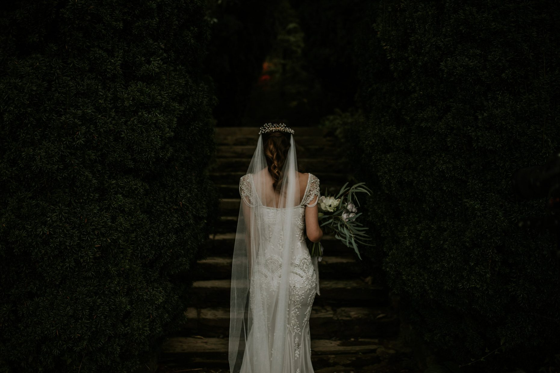 Wedding photographer in Cornwall, a bride is walking up the stairs with a huge bunch of wild flowers in her hair and the veil down her back