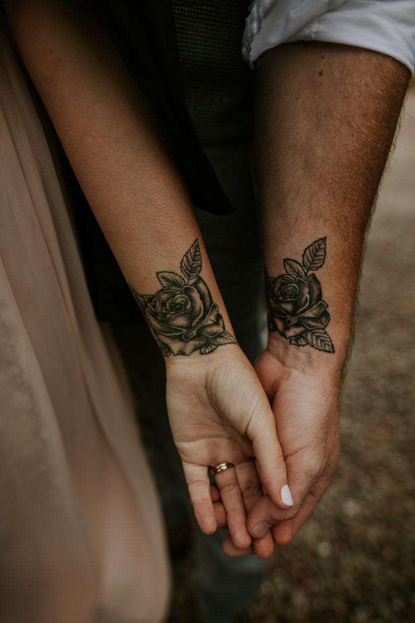 A close up of a wedding couple displaying matching rose tattoos on their wrists-