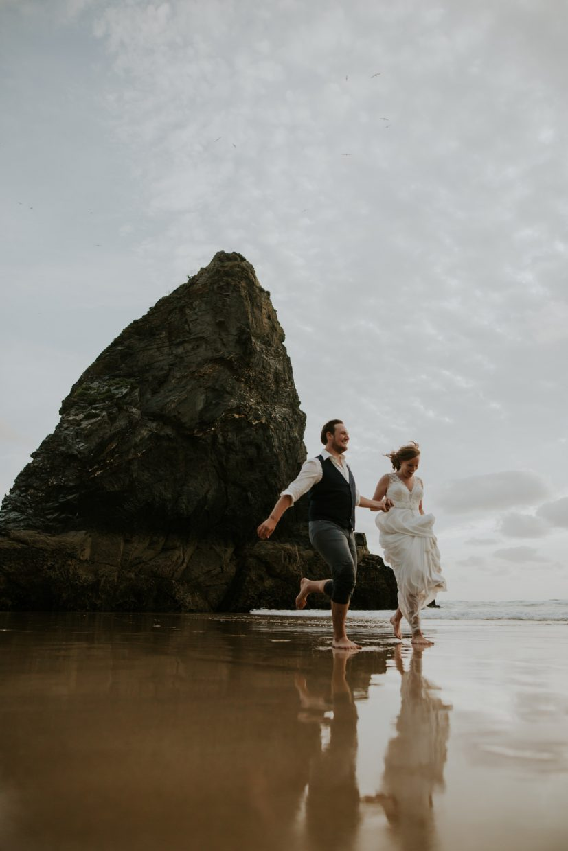 A man and woman dressed in wedding clothes run hand in hand through the sea laughing