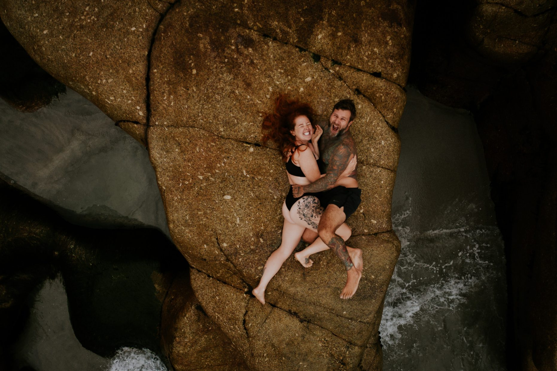 A drone image from above of a couple cuddling closely on the rocks as the waves crash around
