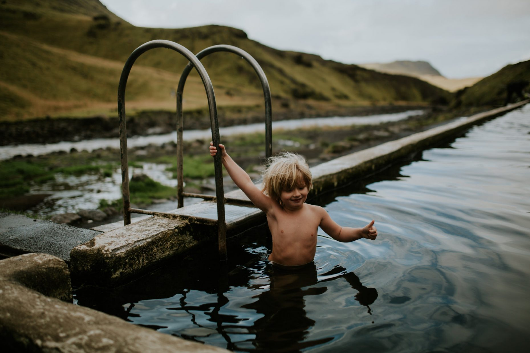 A child is jumping into a hot geothermal pool in Iceland putting his thumbs up at the camera