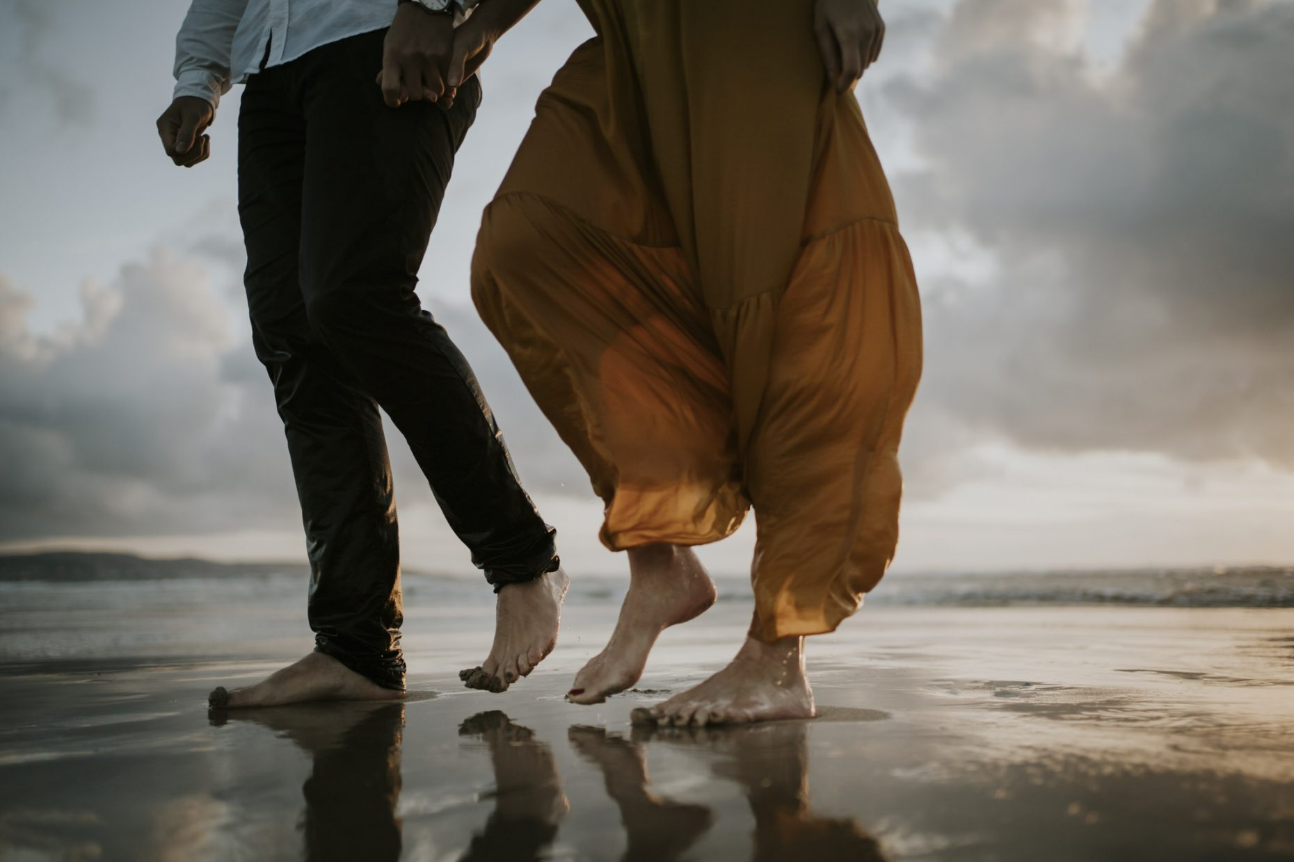 A couple on their elopement in cornwall with their photographer walking barefoot on the sandy beach