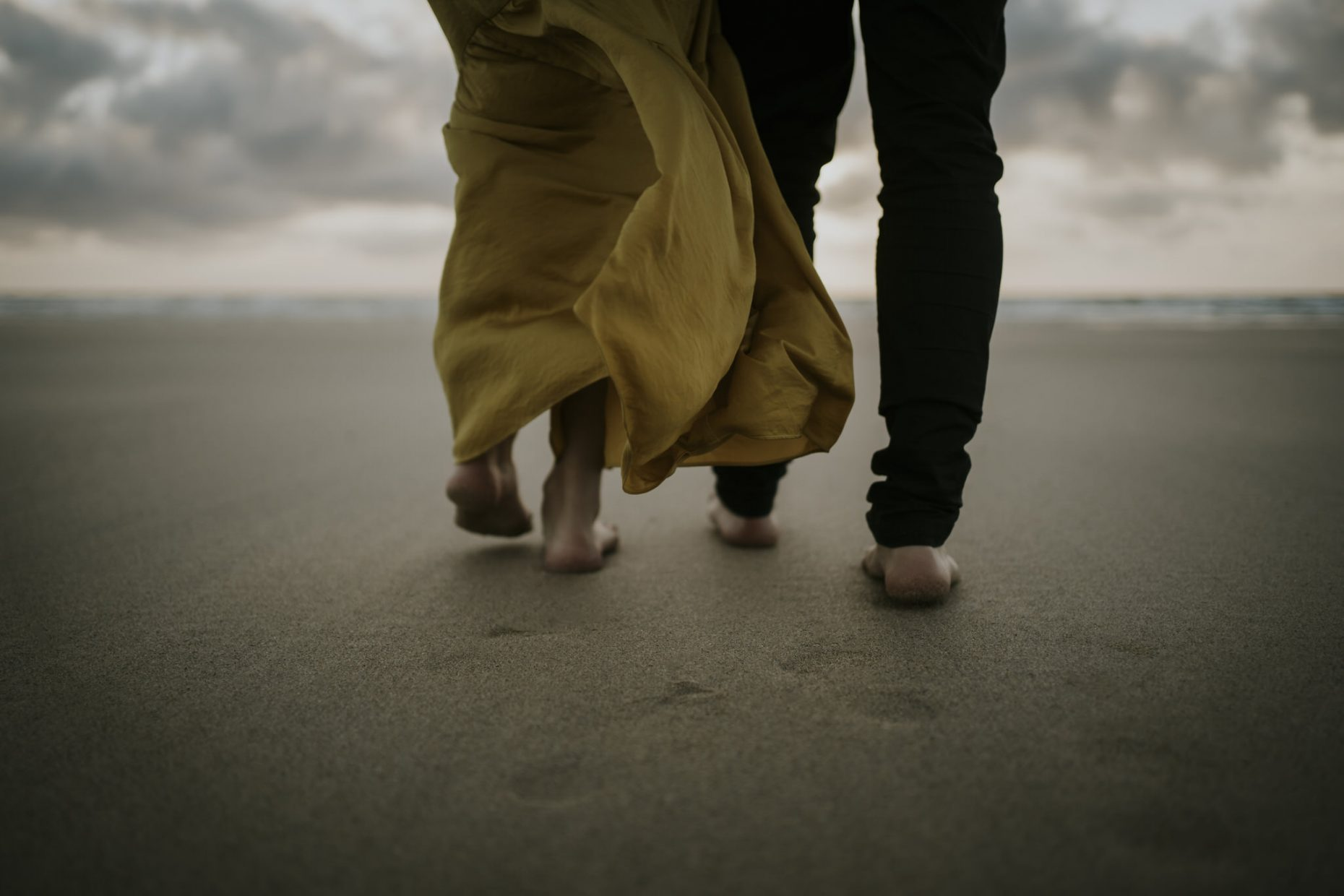 a close up detail shot of a bride and groom barefoot walking in the sand with the sand on their toes and the sun sets behind them with the sea