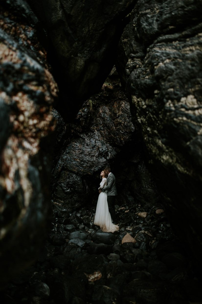 a couple stand in a big sea cave on their elopement looking up to the light as the groom hugs and cuddles the bride around the waist