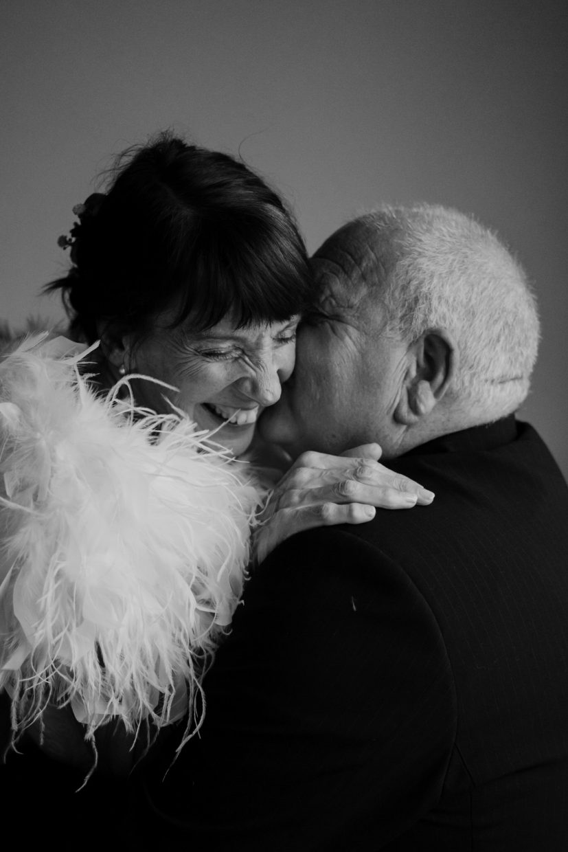 an elderly couple kiss and cuddle closely as the groom kisses her ear and she laughs