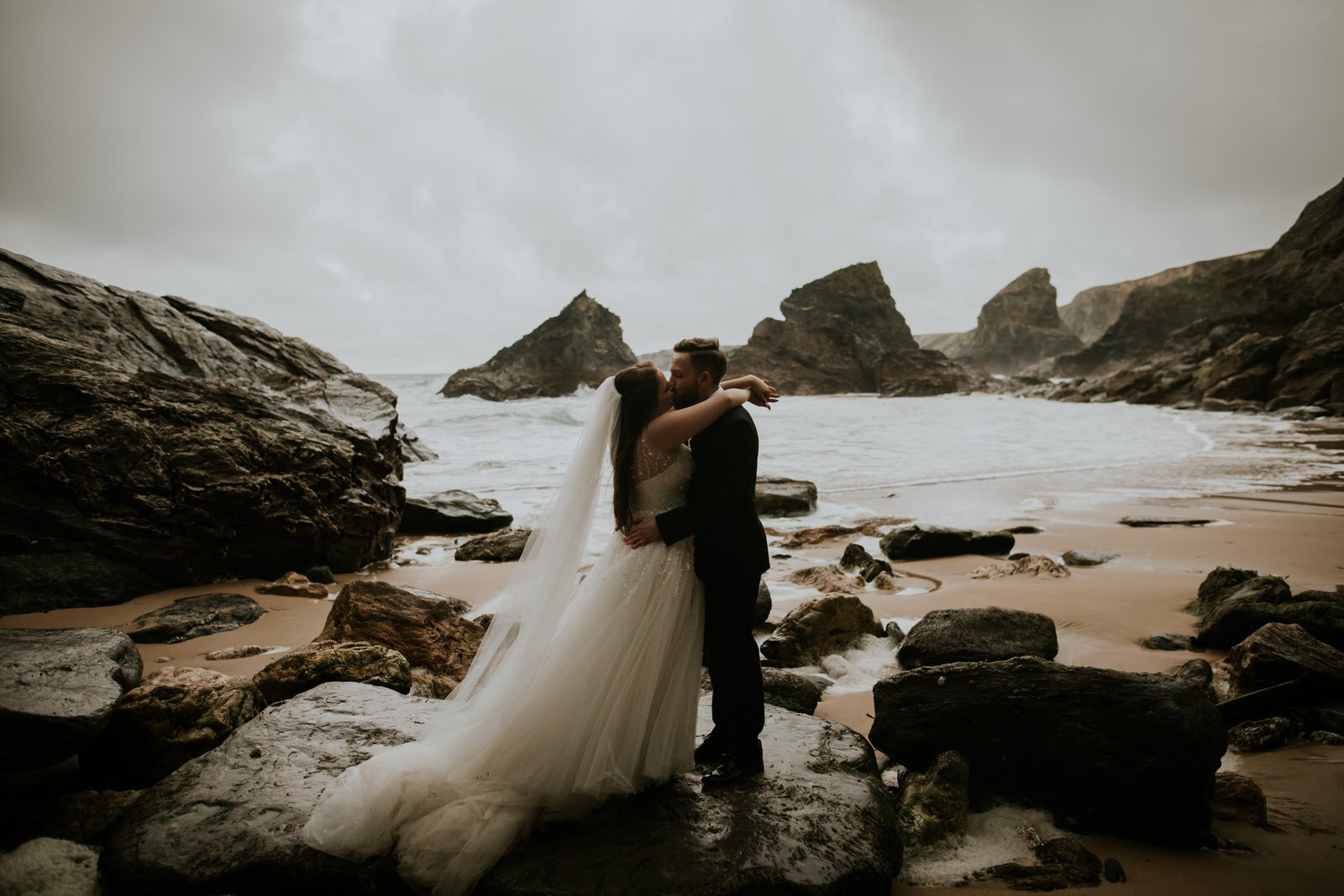 A bride puts her arms around her grooms next and they kiss passionately on a dramatic beach filled with big rocks