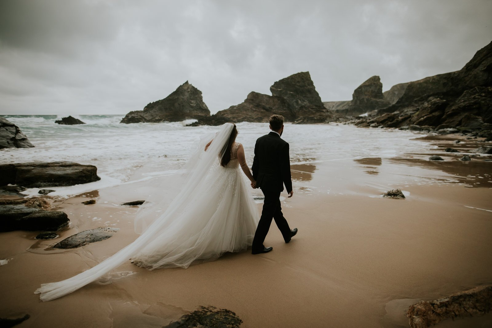 Packages Bride and groom walk hand in hand away from the camera into a wide open dramtic beach, filled with big sea stacks and a long white sandy beach