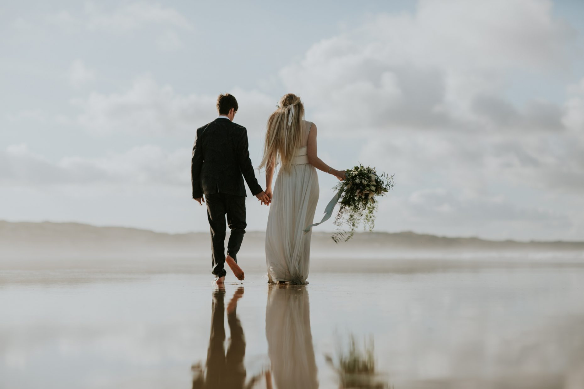 bride and groom walk hand in hand away into a hazy beach setting as their reflections can be seen in the sand. The bride holds wild flowers in her hand