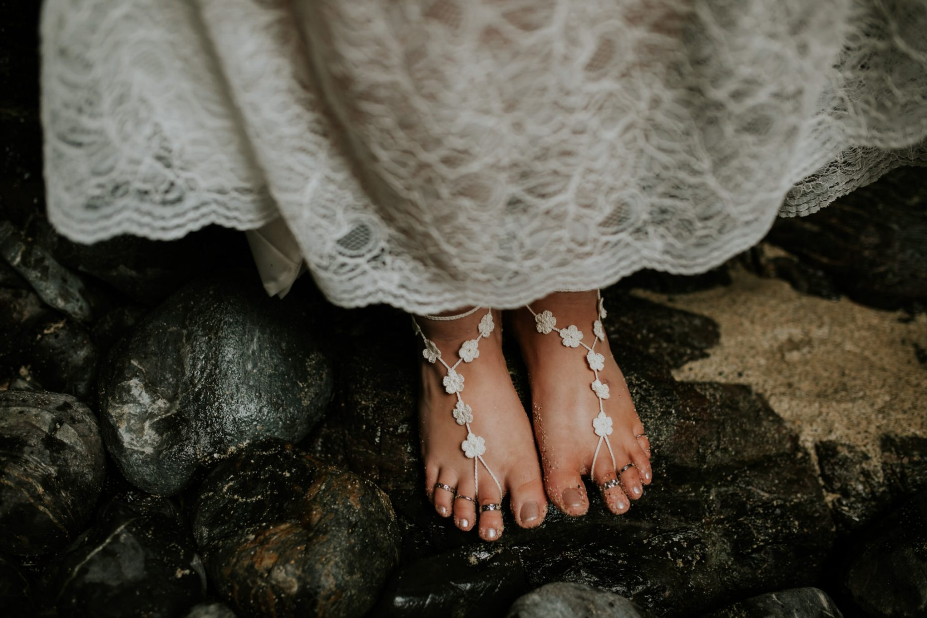 A close up picture of a bride barefoot on the beach