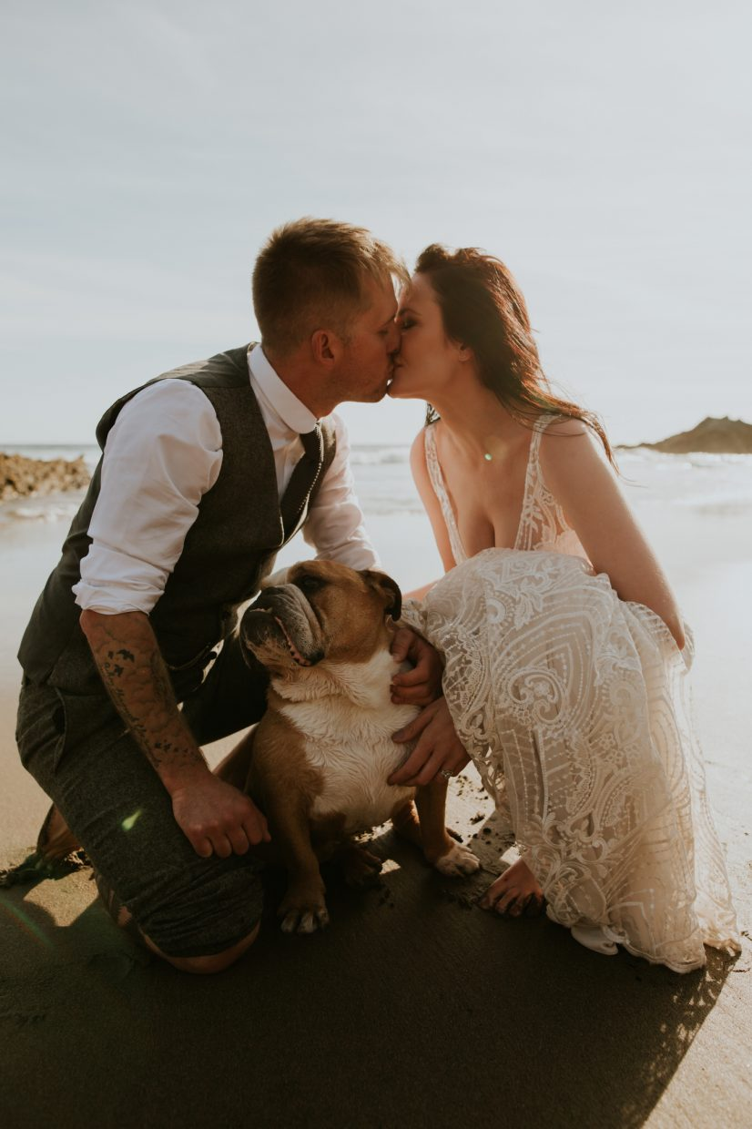 a couple crouch down with their bulldog on the beach on their wedding as they kiss over the dogs head barefoot