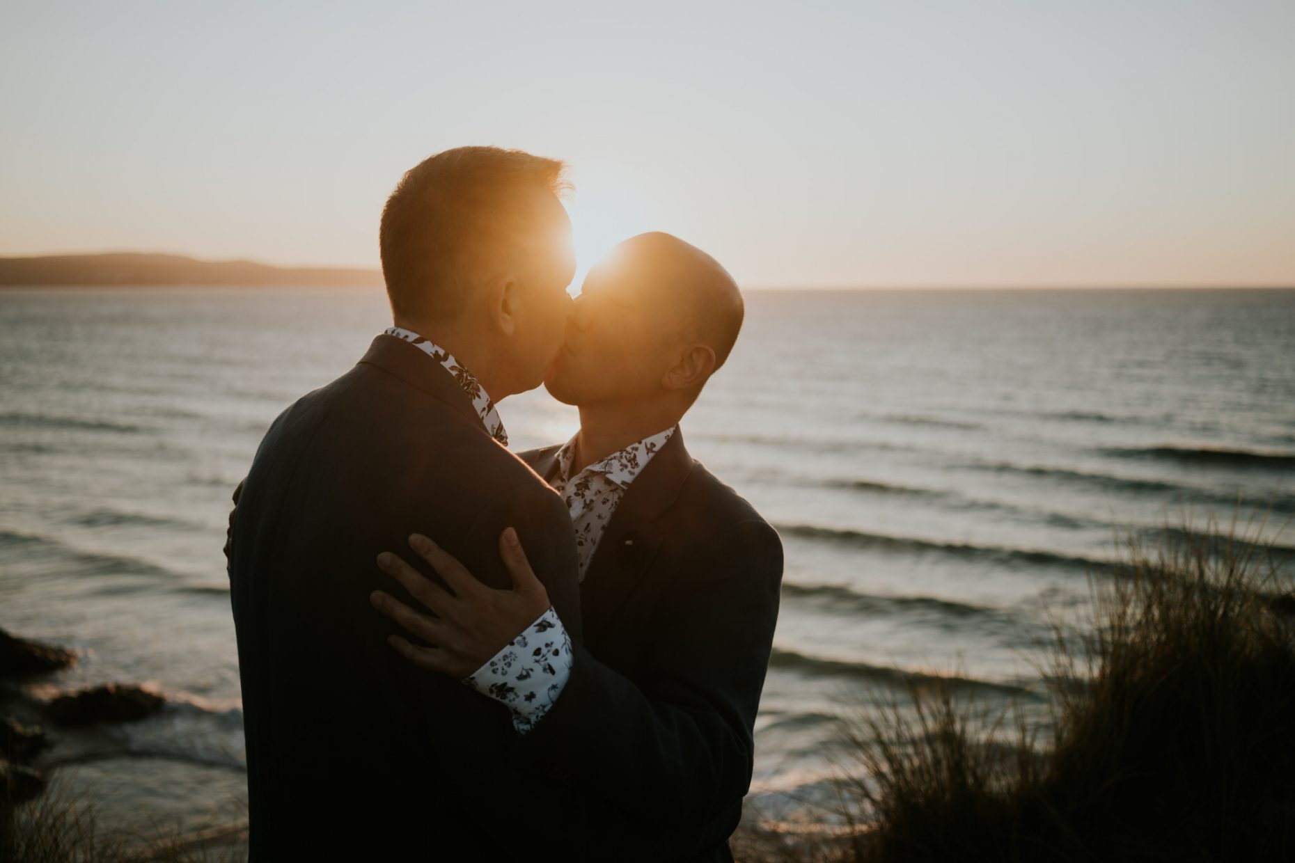 two men kiss on a dramatic beach as the sun sets behind them lighting up the sea