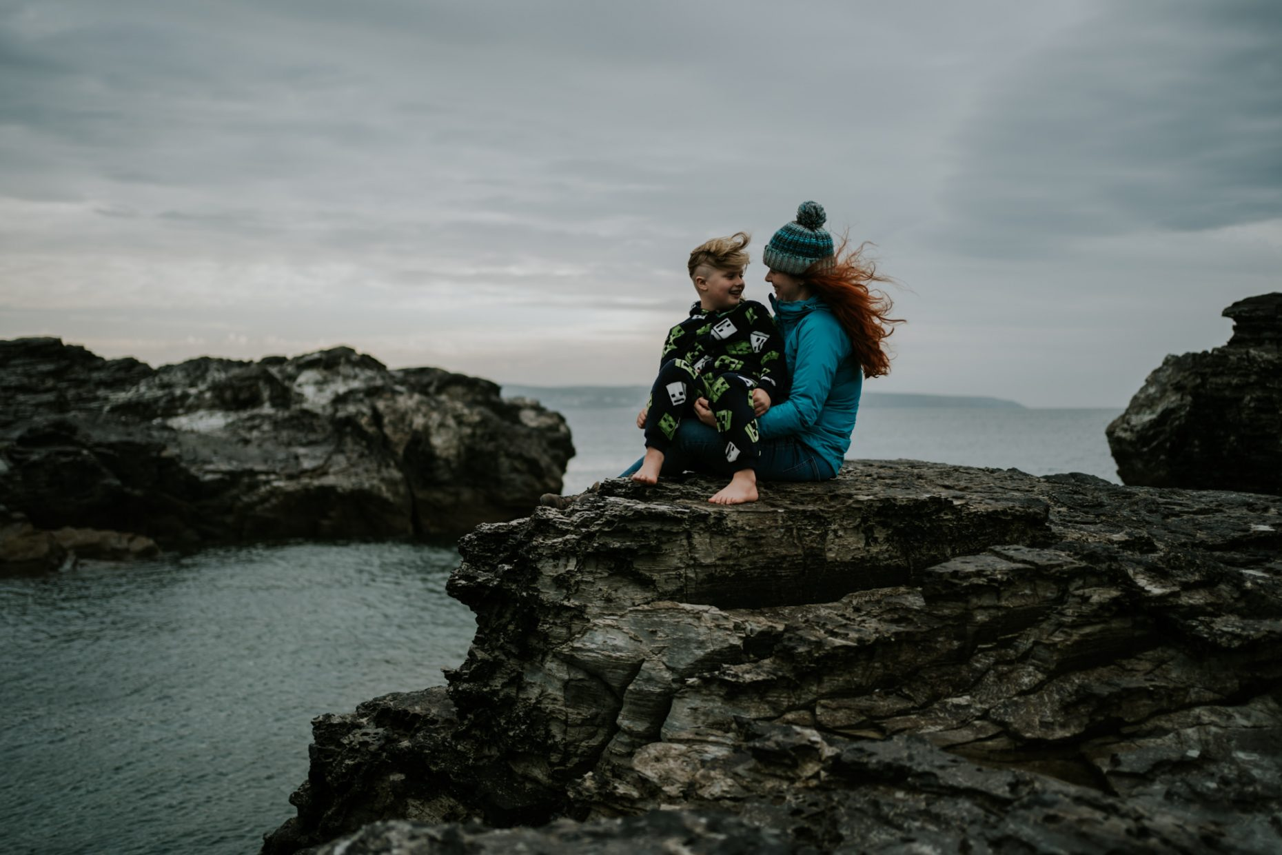 A boy sits on his mothers lap on the edge of a cliff as the wind blows their hair and they laugh together with the sea behind