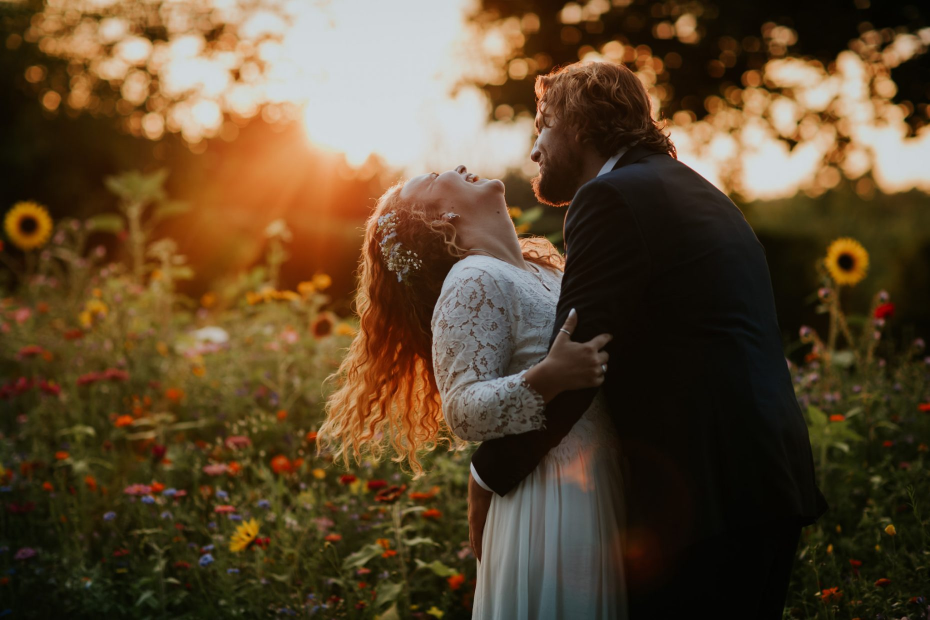 a bride and groom his and laugh as the bride throws her head back and there is sunflowers surrounding them
