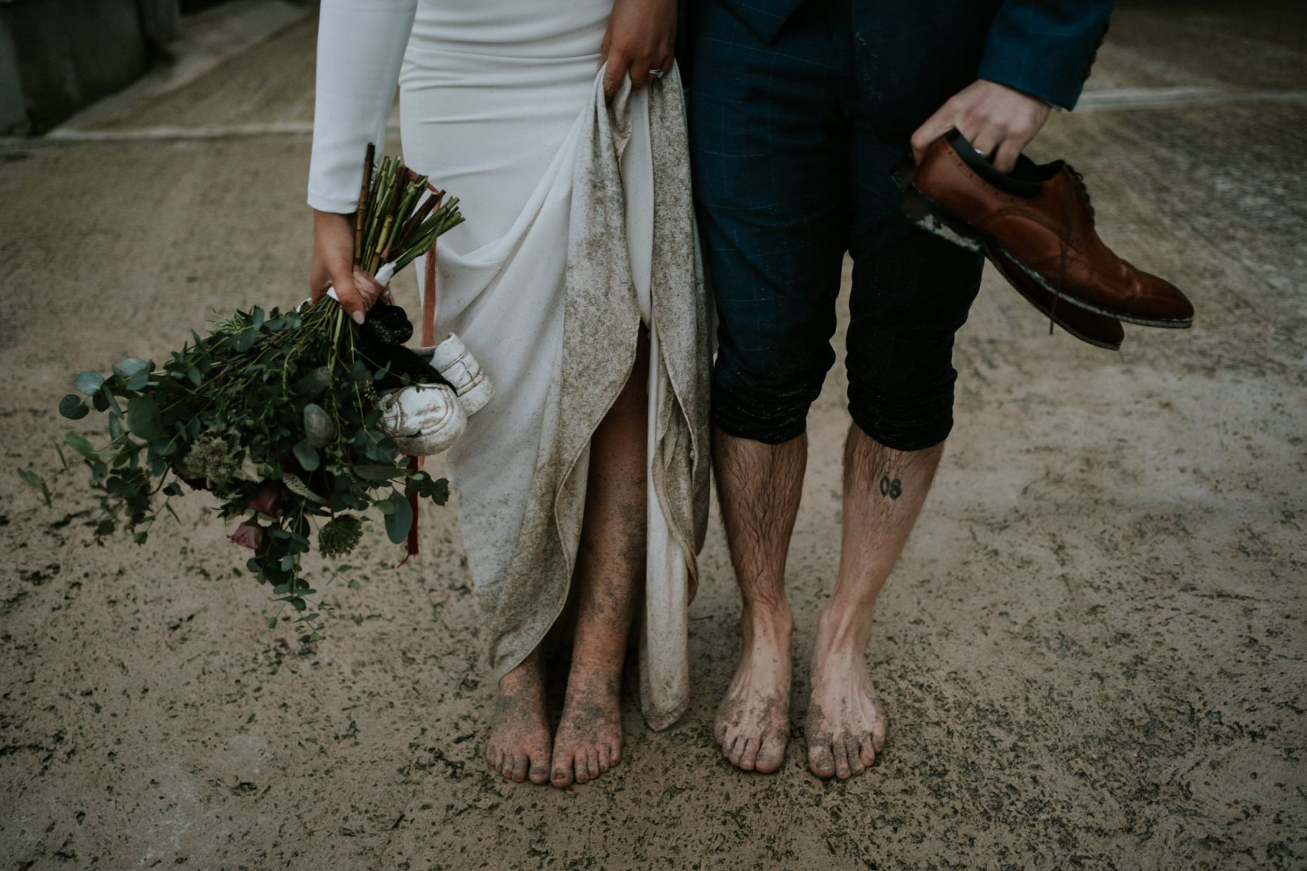 a bride and groom stand barefoot covered in wet sand and dirty holding their shoes and bouquet in their hands
