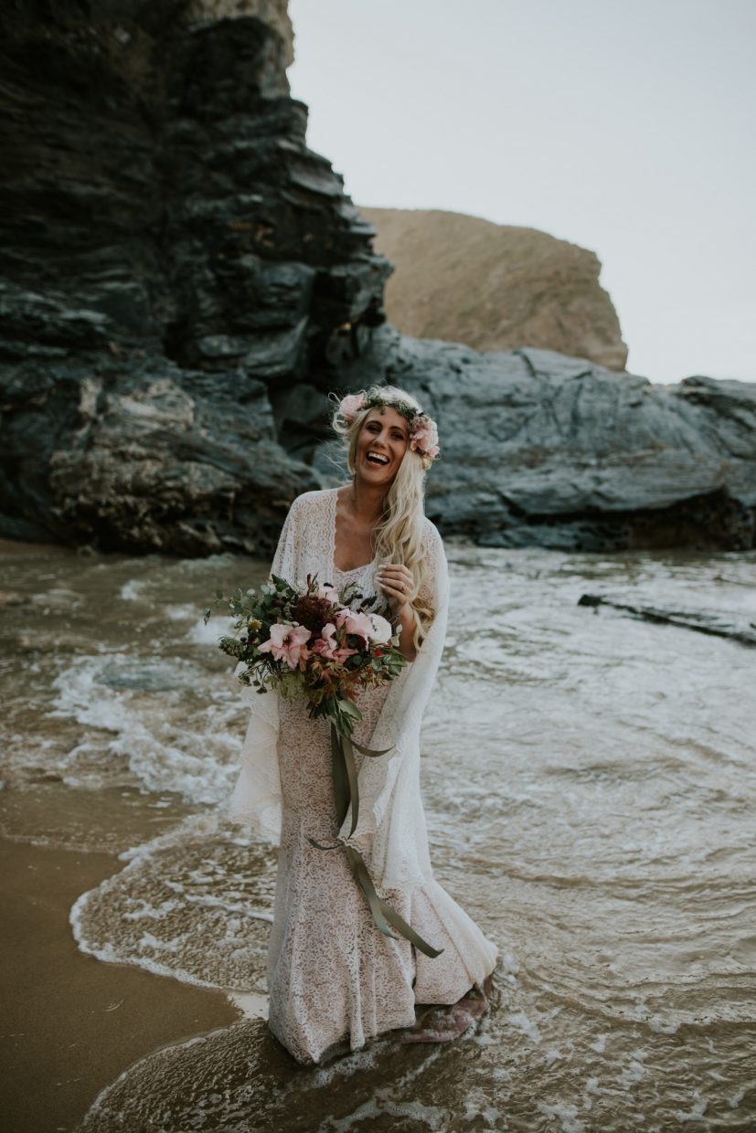 bride is standing in the sea in her wedding dress as a wave crashes around her, she is holding a big bunch of wild flowers and smiling