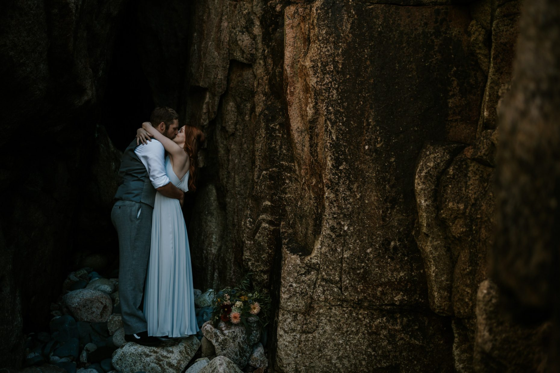 a couple embrace passionately with the brides arms wrapped around the groom in a tin min in cornwall on the coast