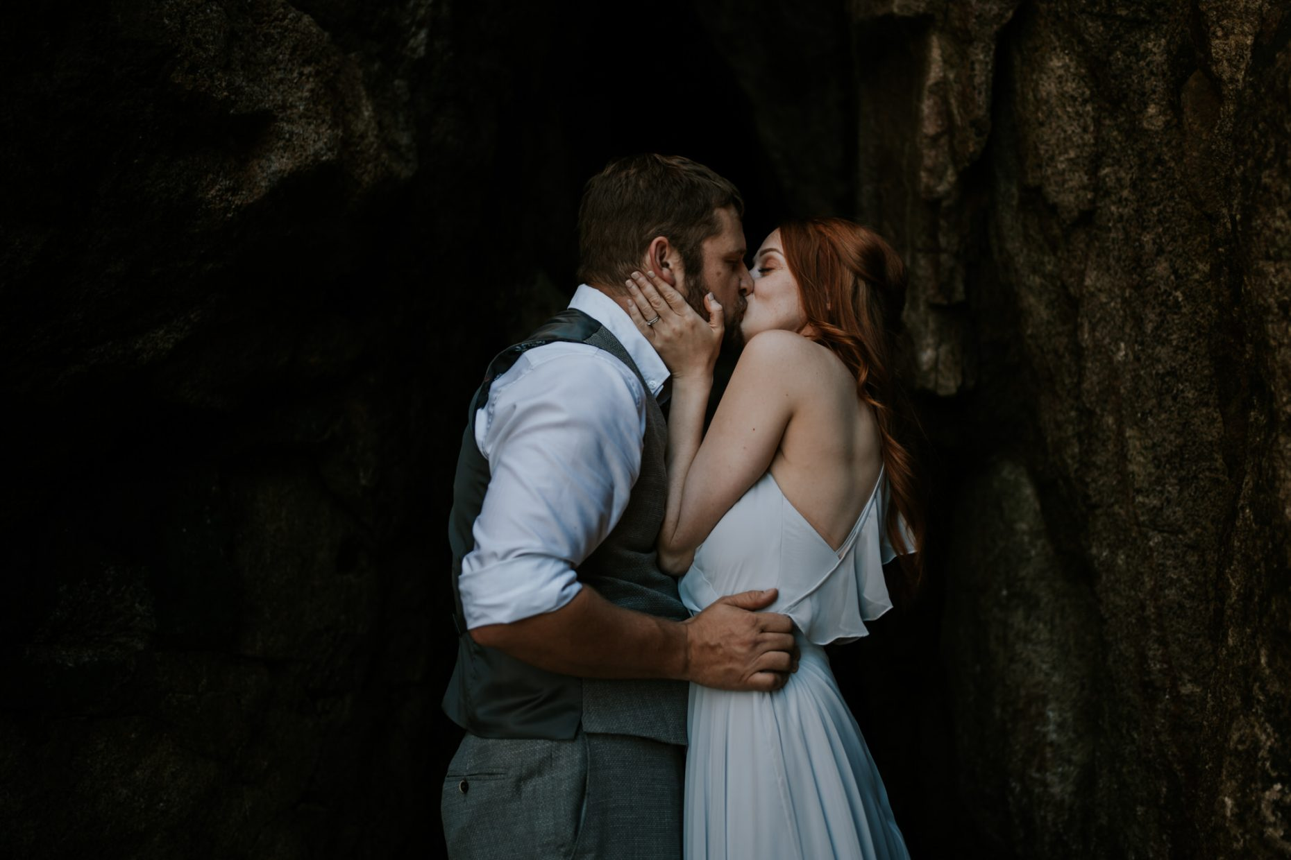 After having an elopement package in cornwall the bride kisses groom passionately in a sea cave, her hand grab his face as he pulls her close with his hands tightly around her waist
