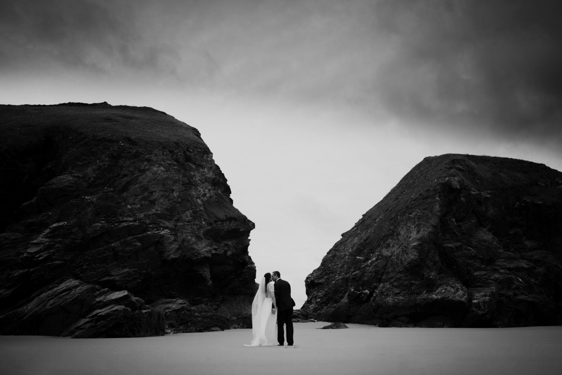 bride and groom kiss in a dramtic landscape, white sandy beach with huge black rocks frame them with big dark clouds above them