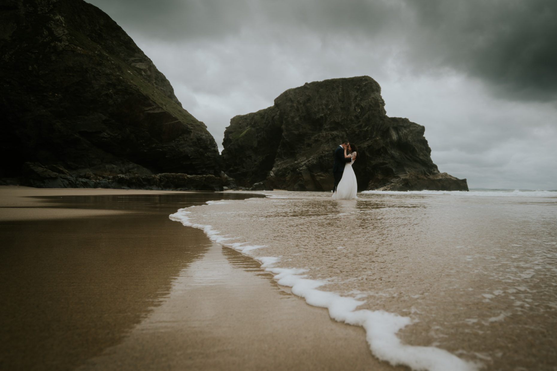 Micro wedding couple stand in the water on their wedding day as the waves splash them as they kiss