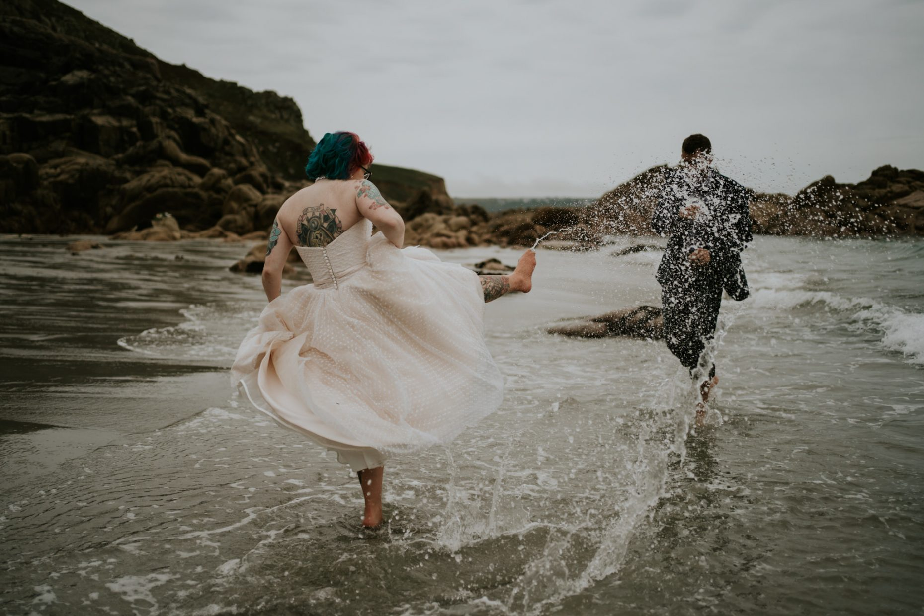 A bride kicks up her leg and splashes her groom as they run laughing through the water