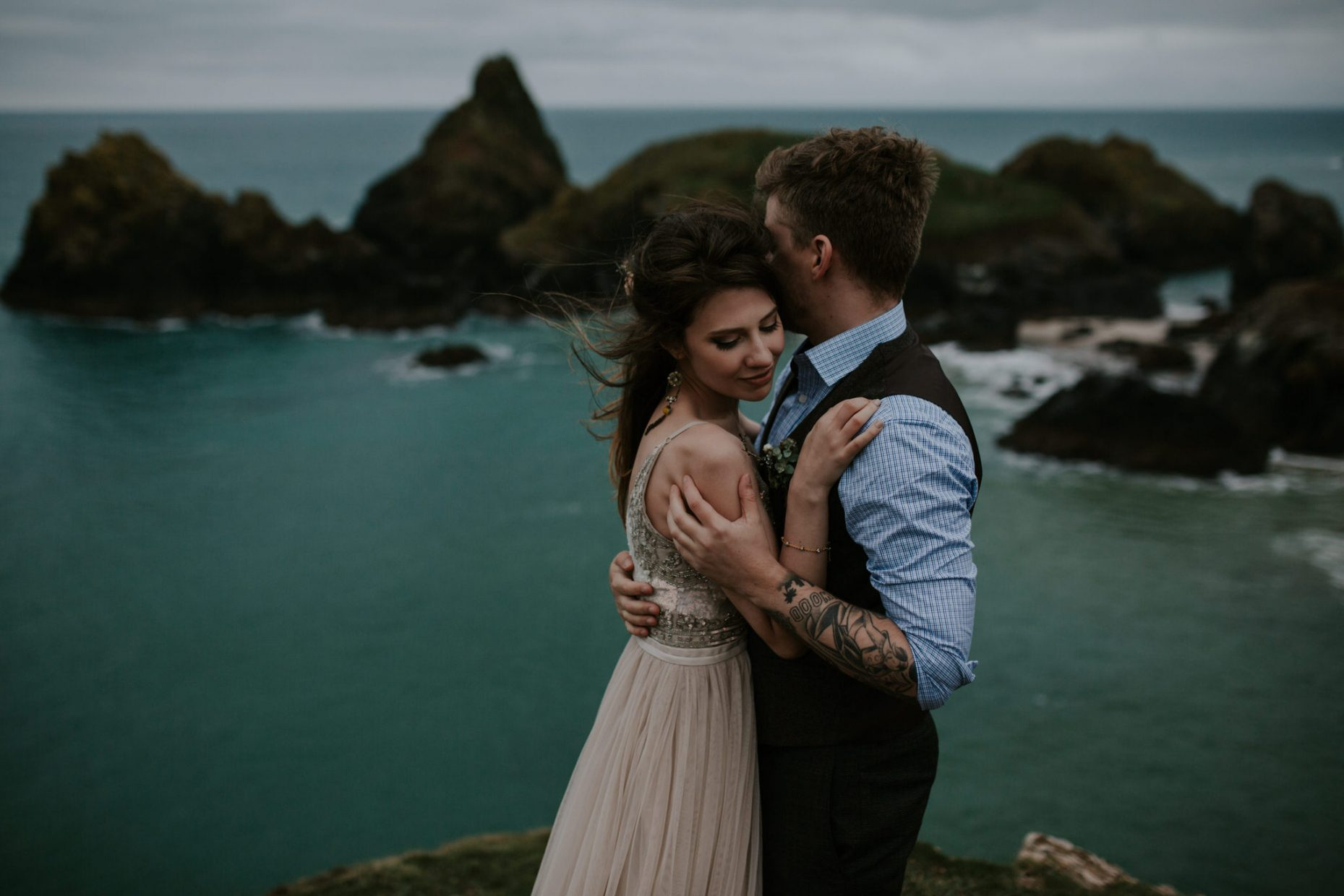 A couple embrace on their engagement shoot in Kynance cove, the huge rocks and clear water frame them