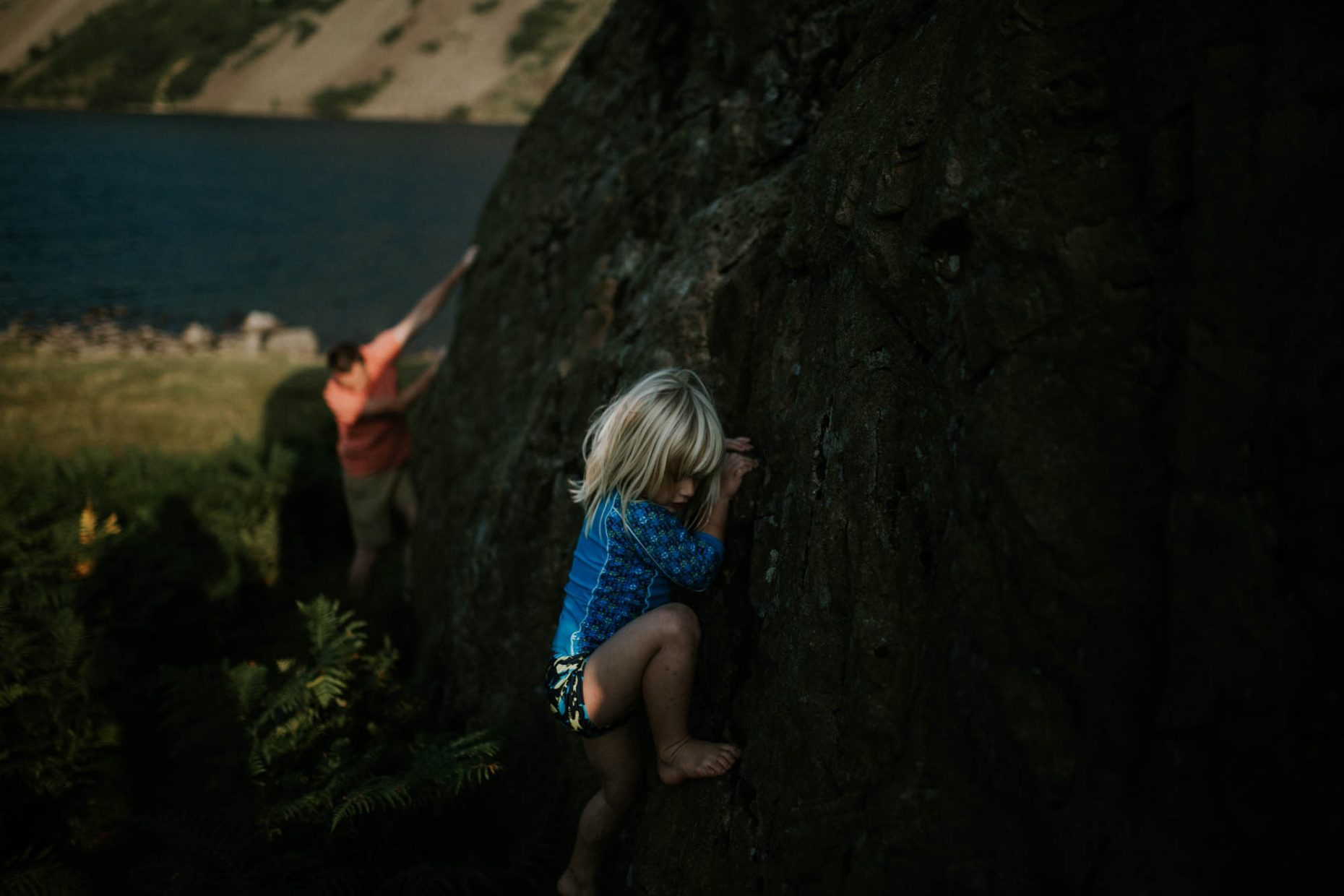 A young boy is bouldering with his father on a rock barefoot and his face pulling a strained expression