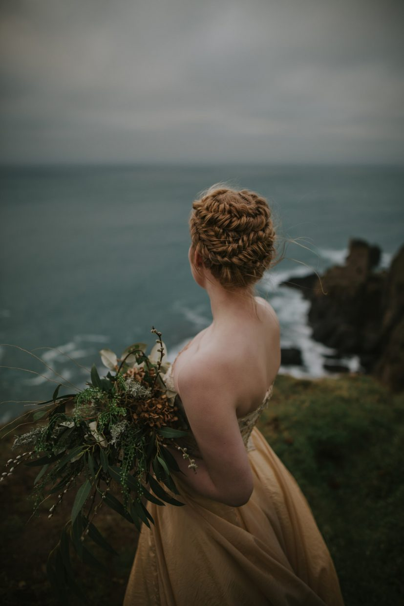 a bride stares out to sea her hair in braids wearing a gold wedding dress with wild flowers in her hand