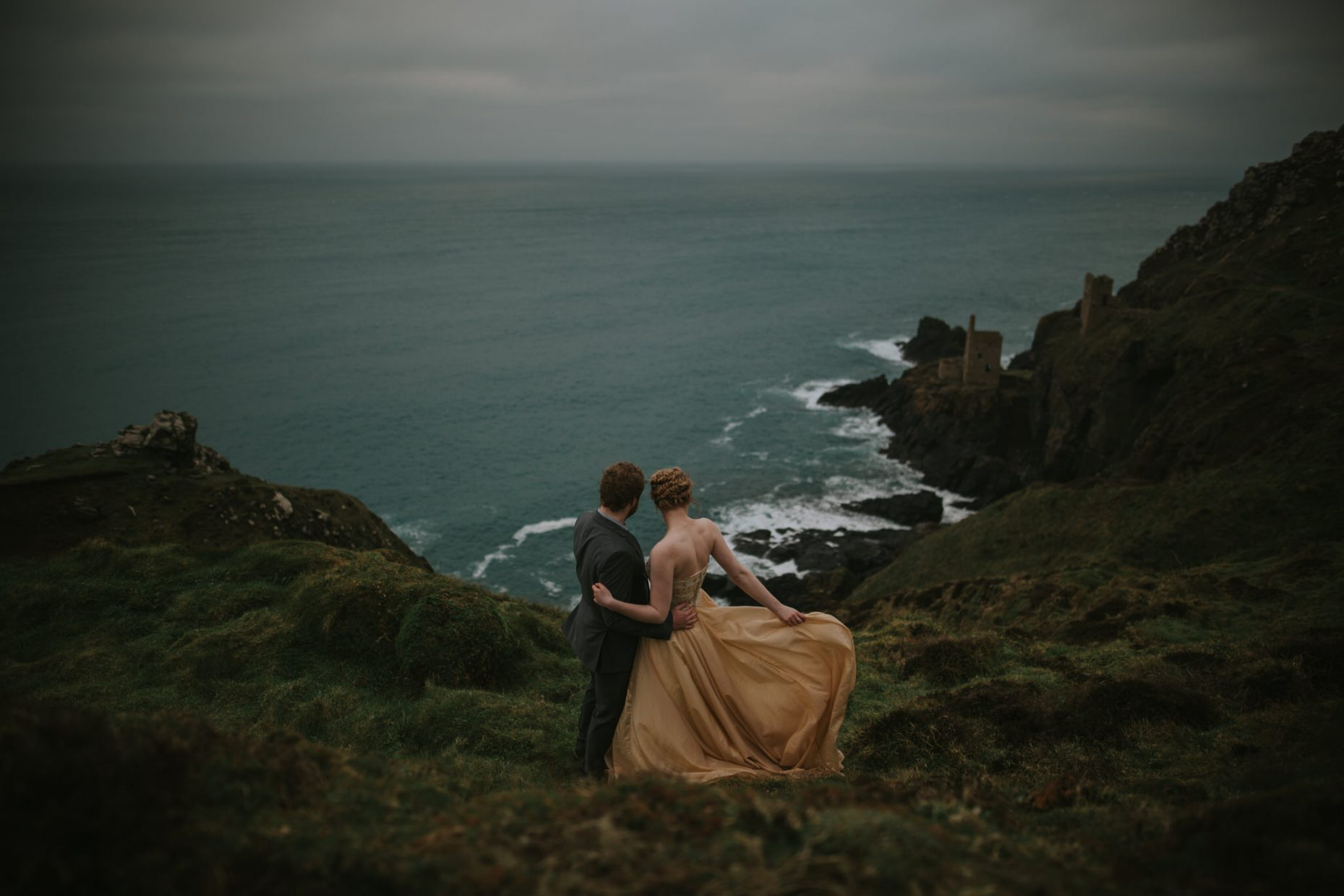 ELOPMENET PHOTOGRAPHER A couple hug on the edge of a cliff during their wedding in Cornwall, the brides golden dress is blowing in the wind