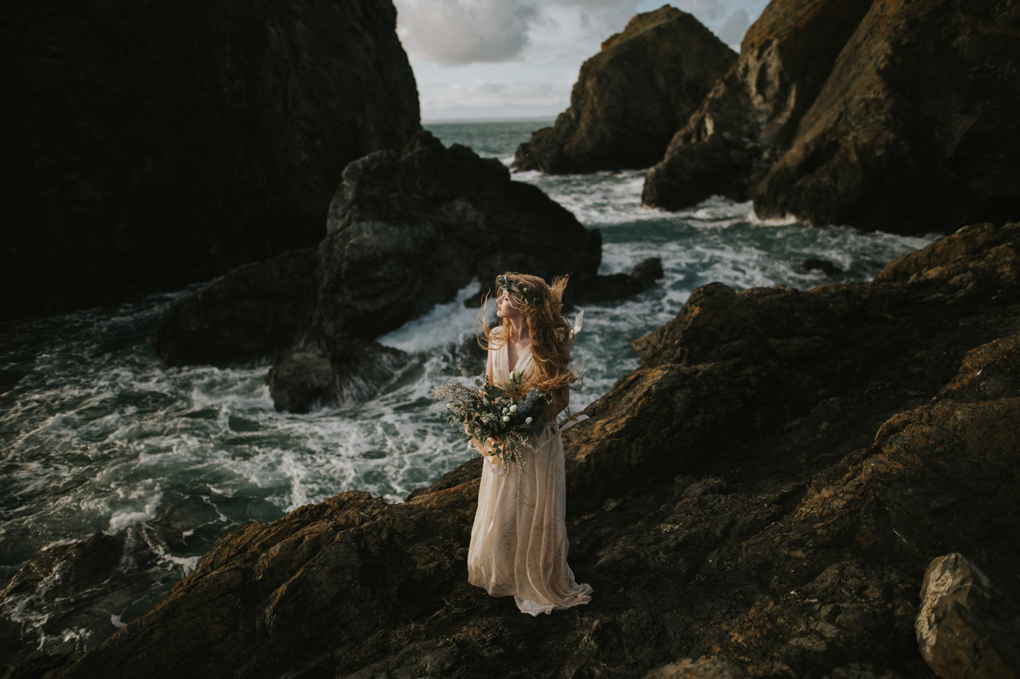 Elopement Photographer Uk shoot a beautiful bride on her wedding day on a rough cliff in Cornwall