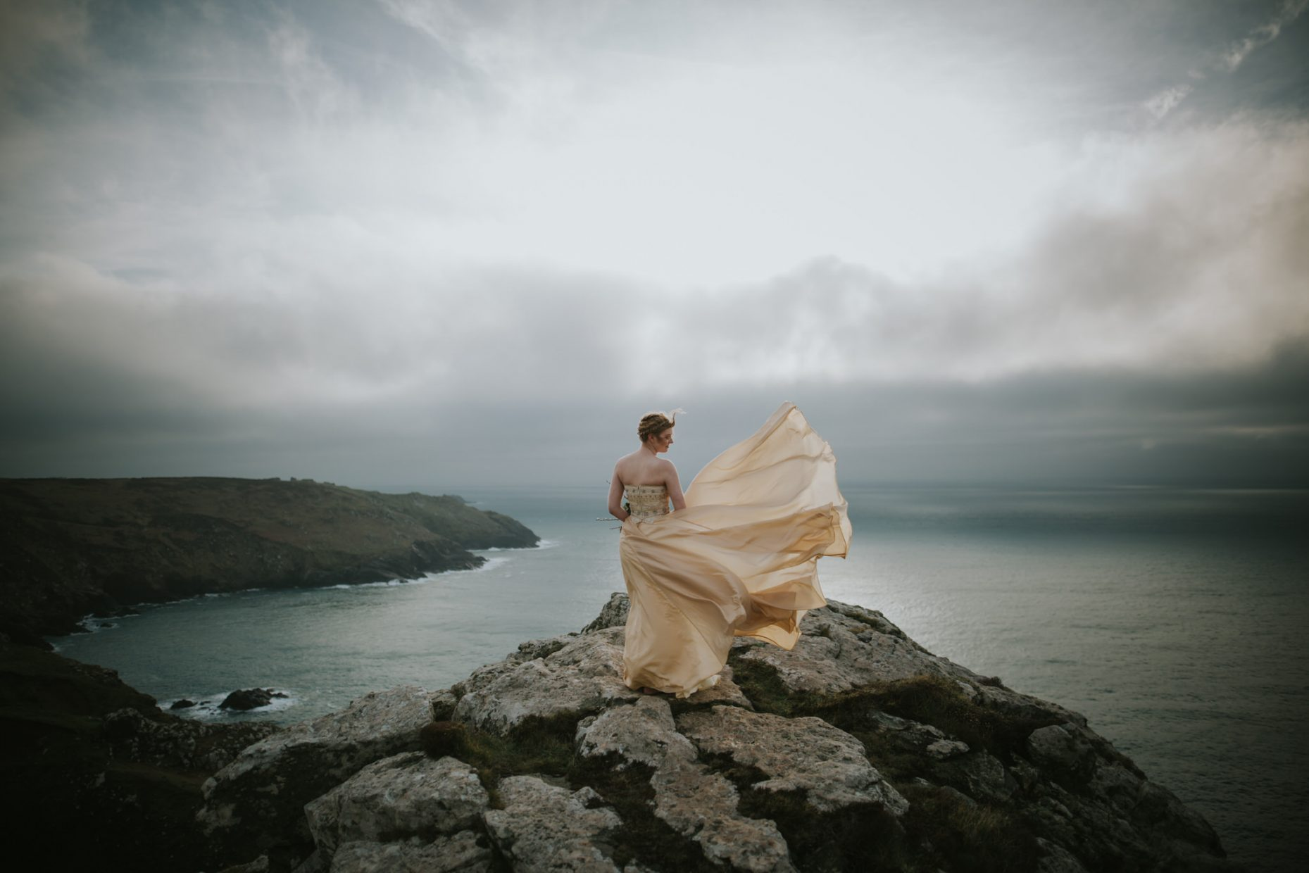 bride stands on the cliffs at botallack mine staring out to sea, looking at the moody grey clouds as the wind blows up her golden wedding dress on her elopement package in cornwall