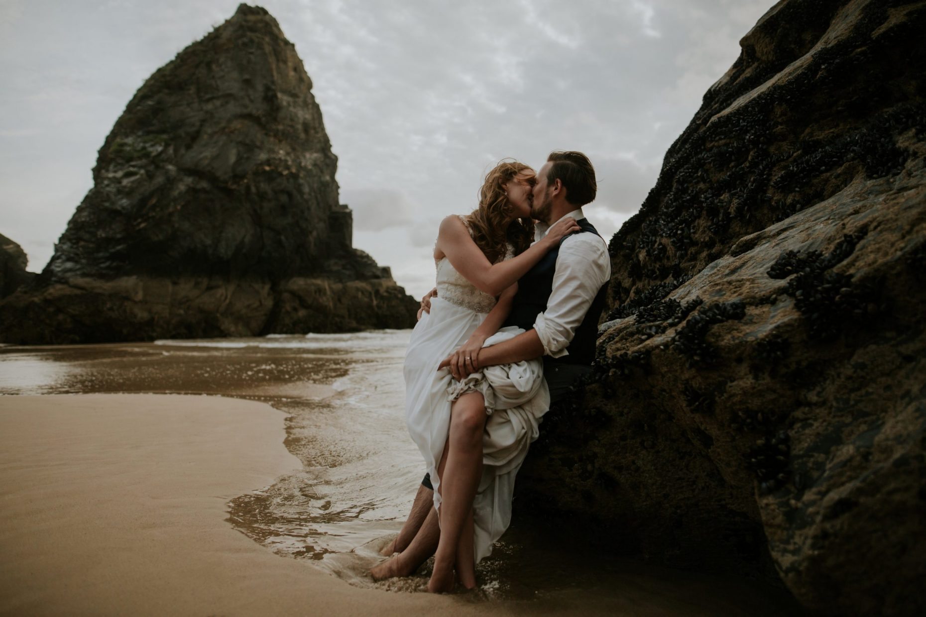 A bride sits on her grooms lap on a rock, they are barefoot and the waves crash around them as they kiss