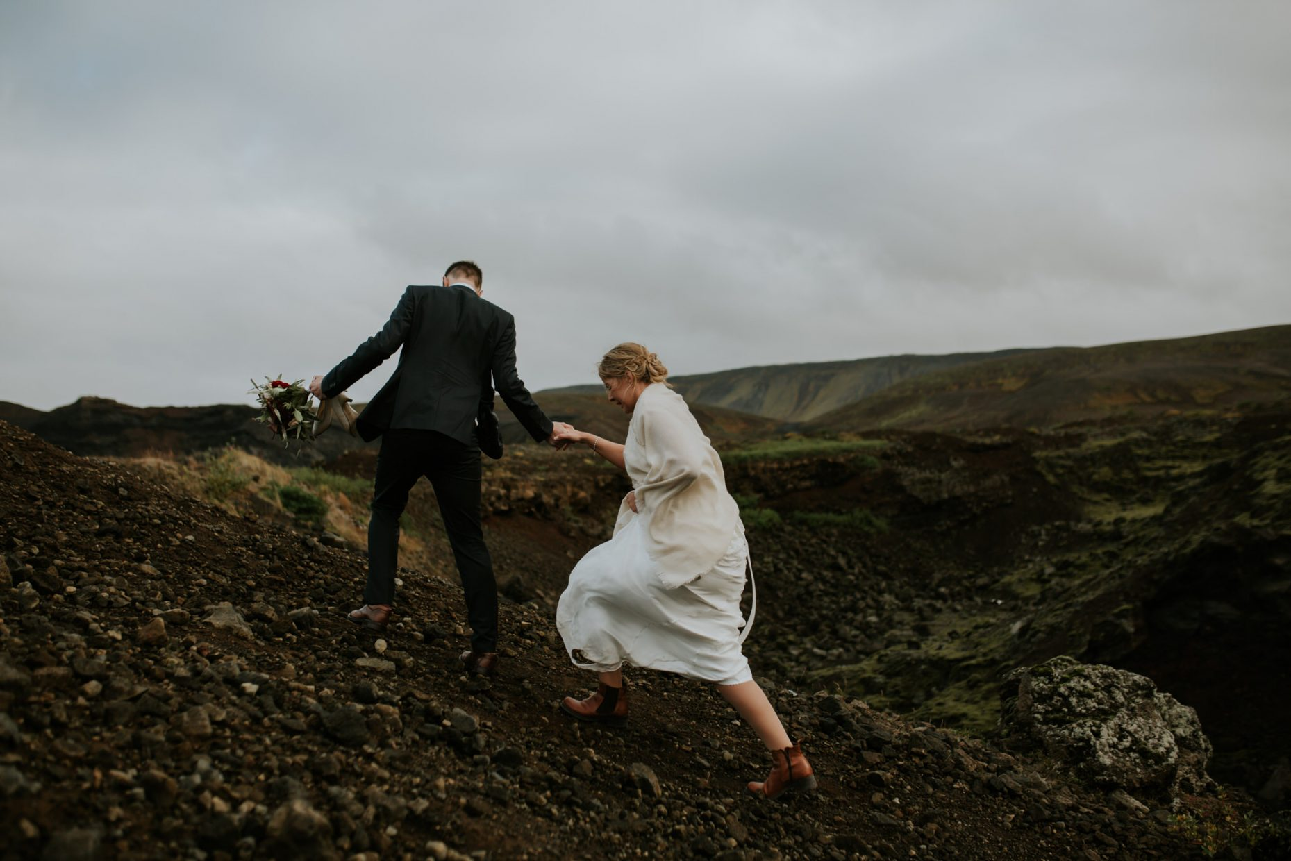 a groom hold a brides hand and helps her up a steep hill and holds her bouquet for her