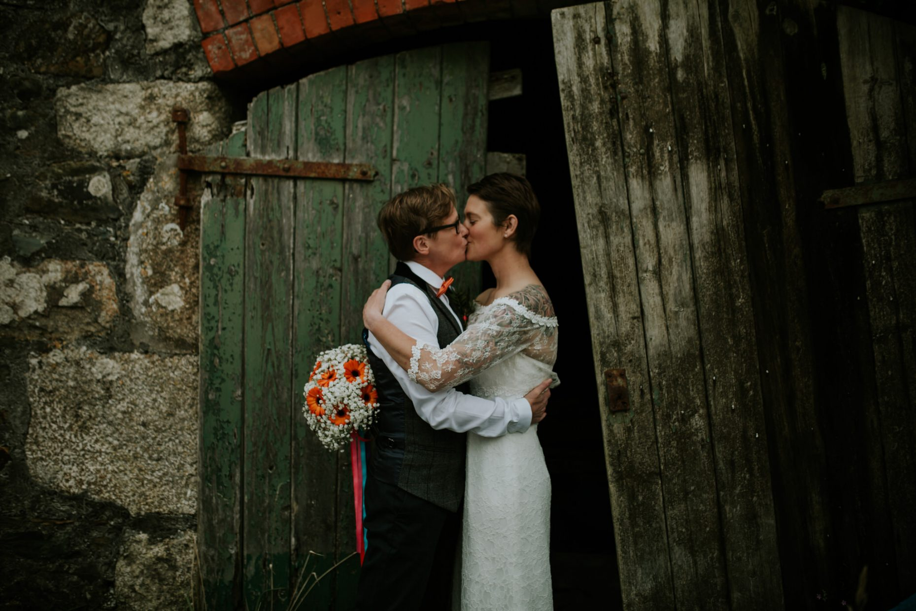 two brides kiss in a doorway with flowers in the one brides hand