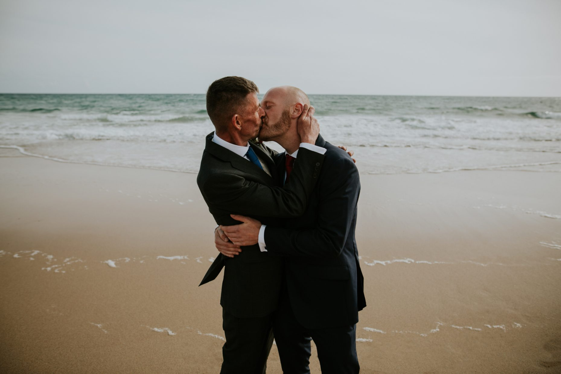a same sex couple kiss and embrace passionately on the beach, putting their hands on each others faces