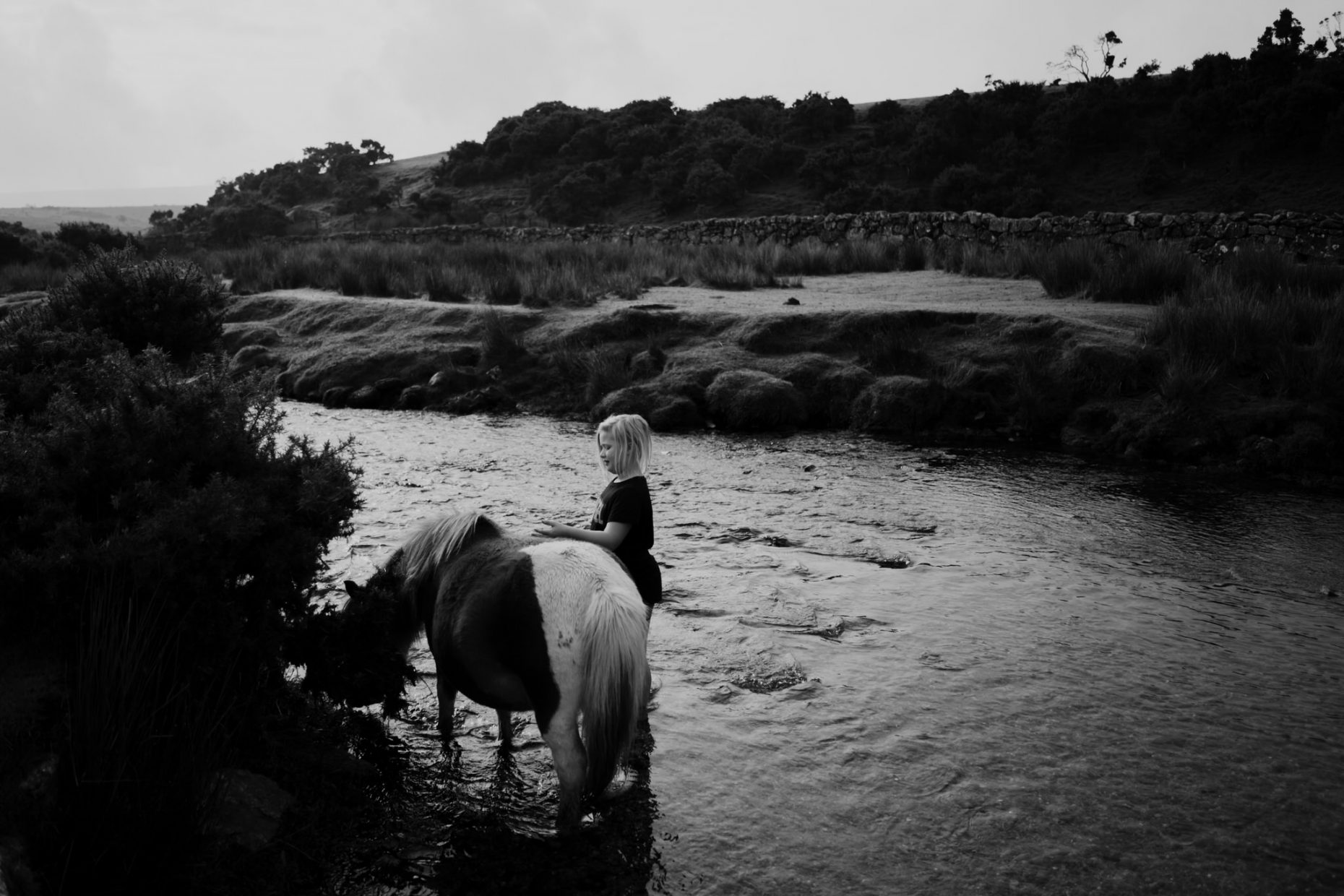 A child is standing in the river talking to a horse as he gently strokes its back