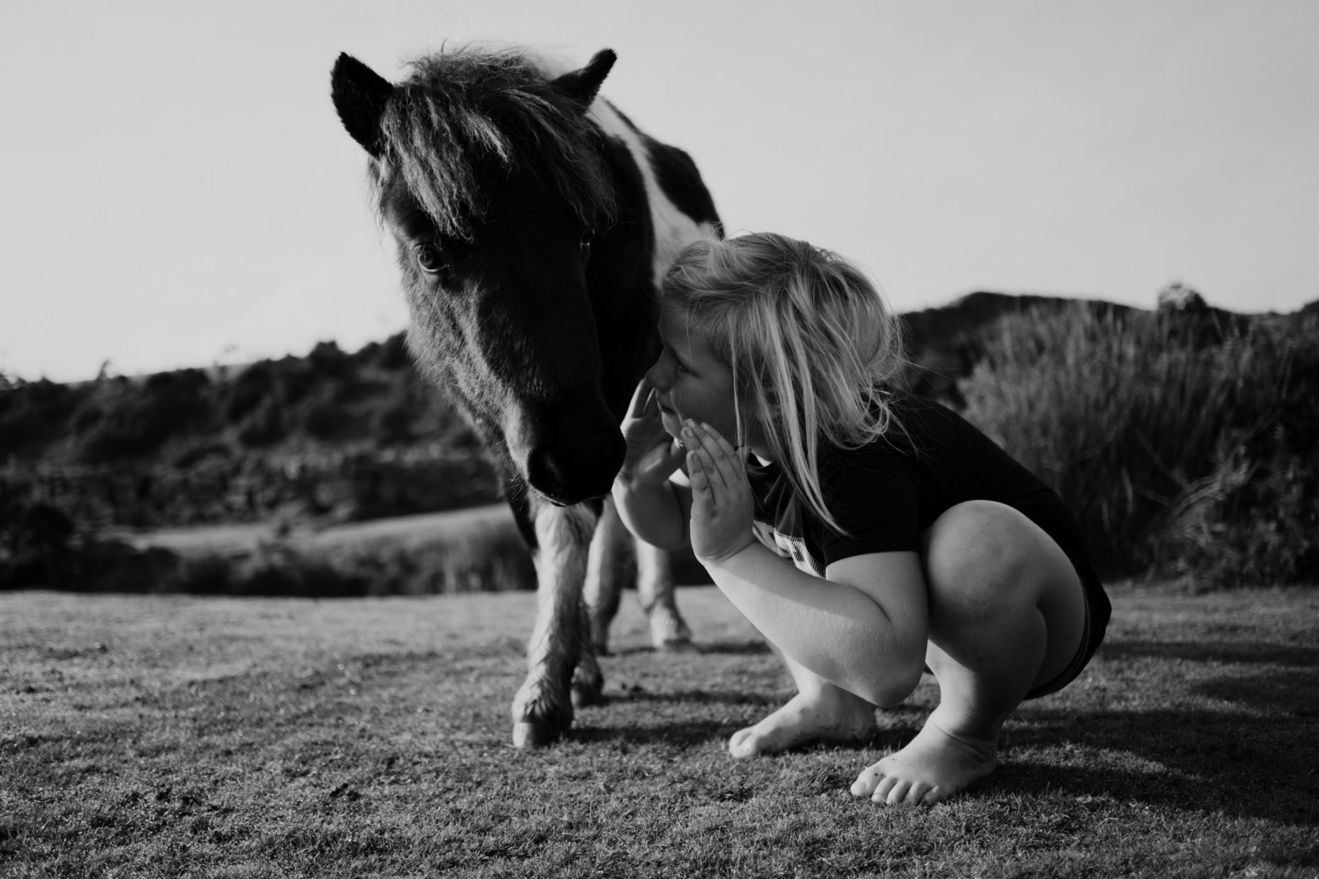 A black and white picture of a boy crouching down and whispering into a horses ear