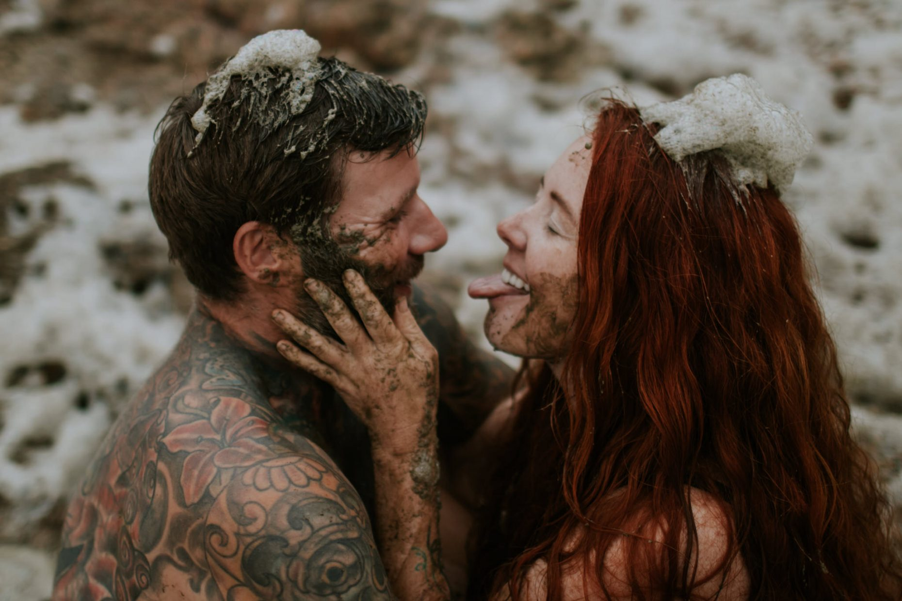a couple sit close together facing each other covered in sea foam as the woman pokes her tongue out playfully at the man