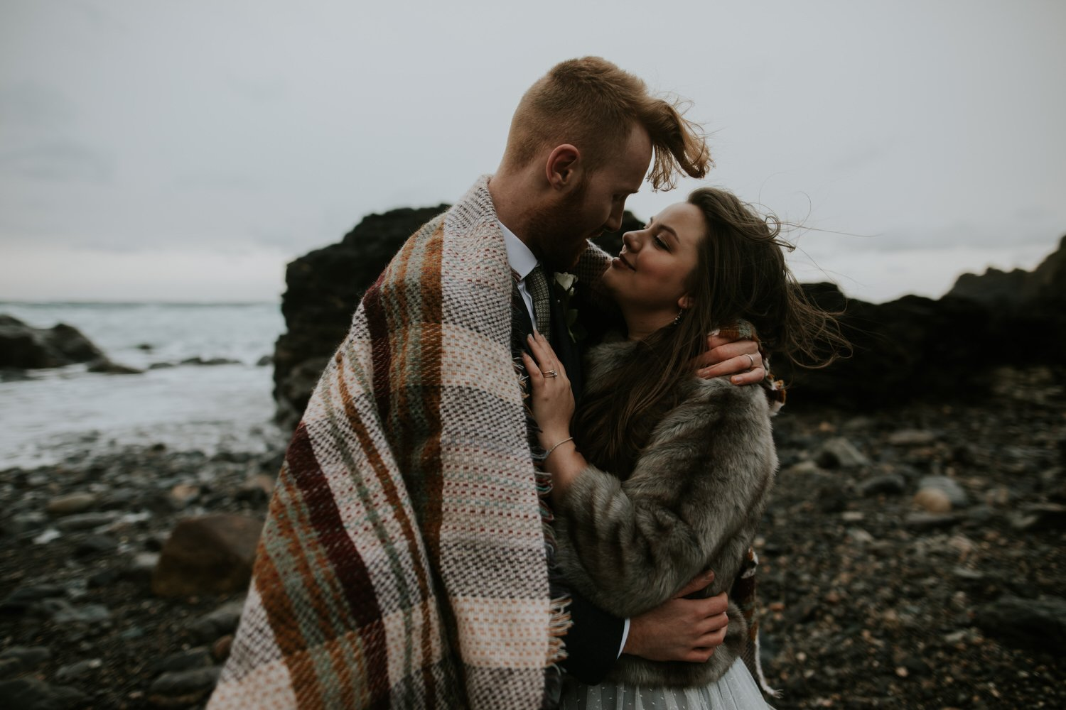 Outdoor Elopement in the UK with a beach Wedding Couple on their wedding day in Cornwall kissing on a beach