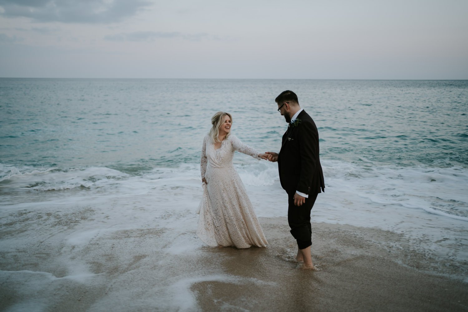 Boho Cornwall Elopement - Couple elope to Cornwall and have fun in the sea at Porthcurno Beach
